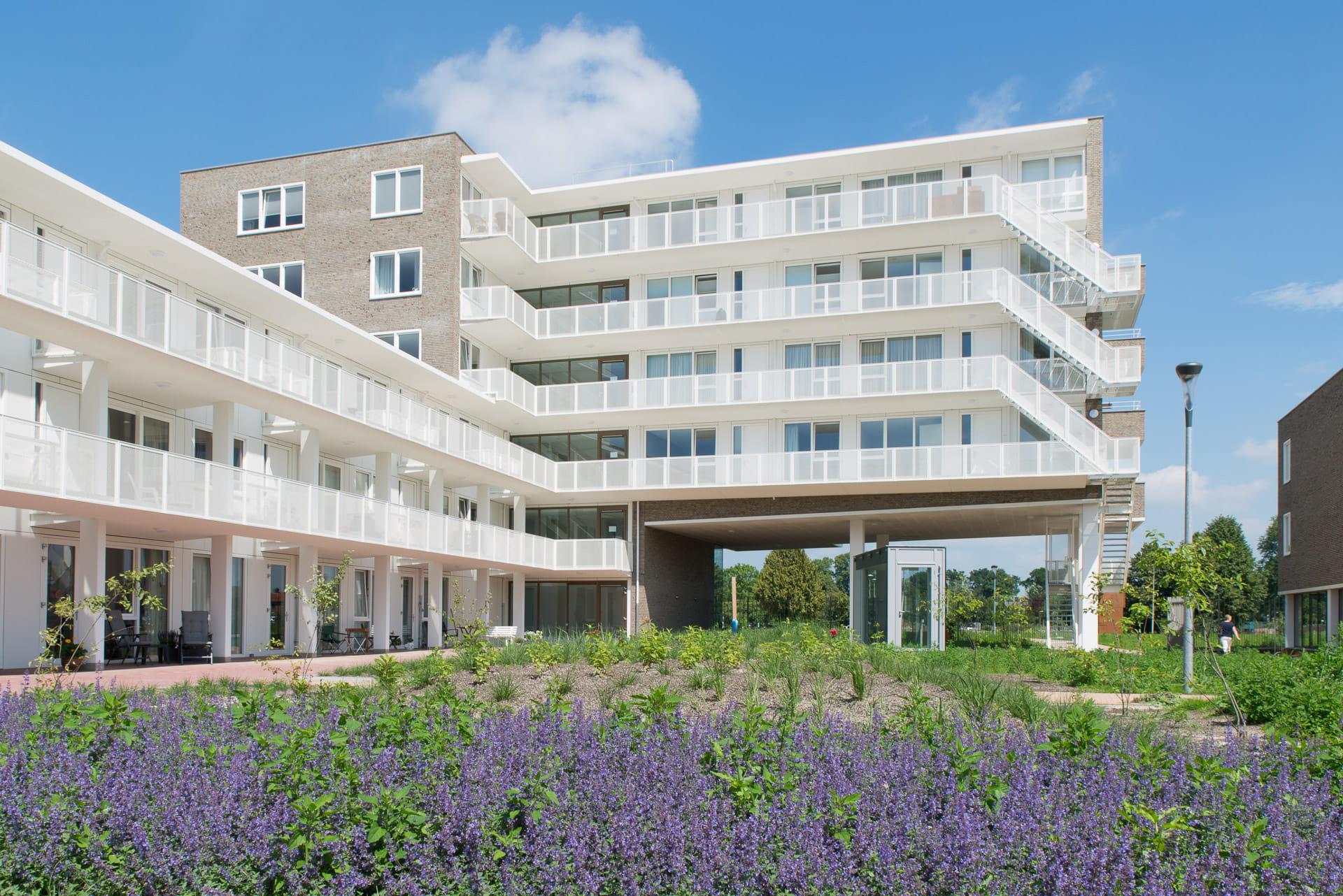 Gebouw met witte gallerijen met lavendel op voorgrond