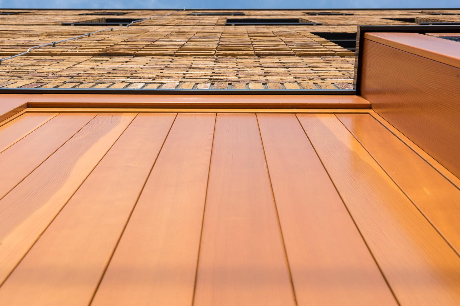 Gevel van onderen bekeken met een gedeelte oranje element en bakstenen erboven