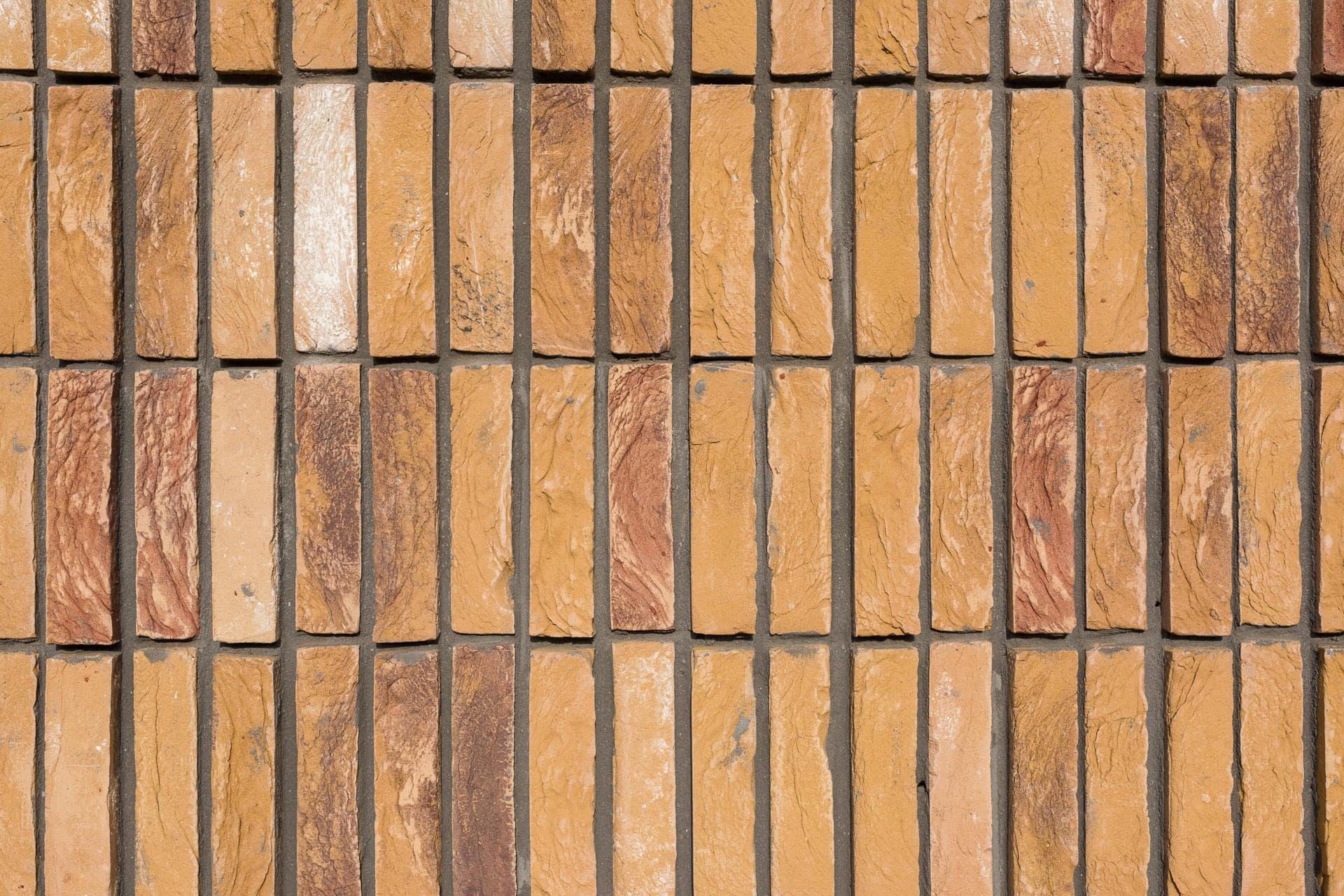 Detail van verticaal metselwerk met een gelige baksteen bij Hoornbeeck College in Rotterdam