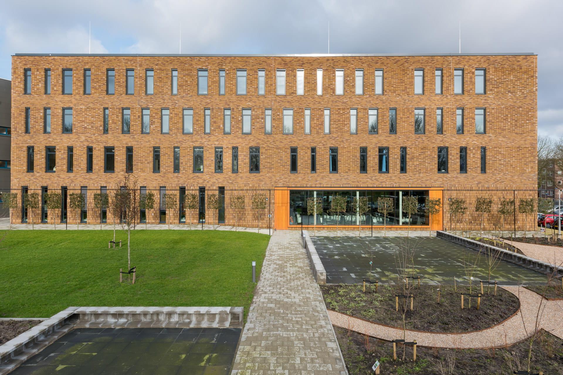 Vooraanzicht van Hoornbeeck College Rotterdam met ramen en vlakken, oranje element in de gevel en tuin op de voorgrond