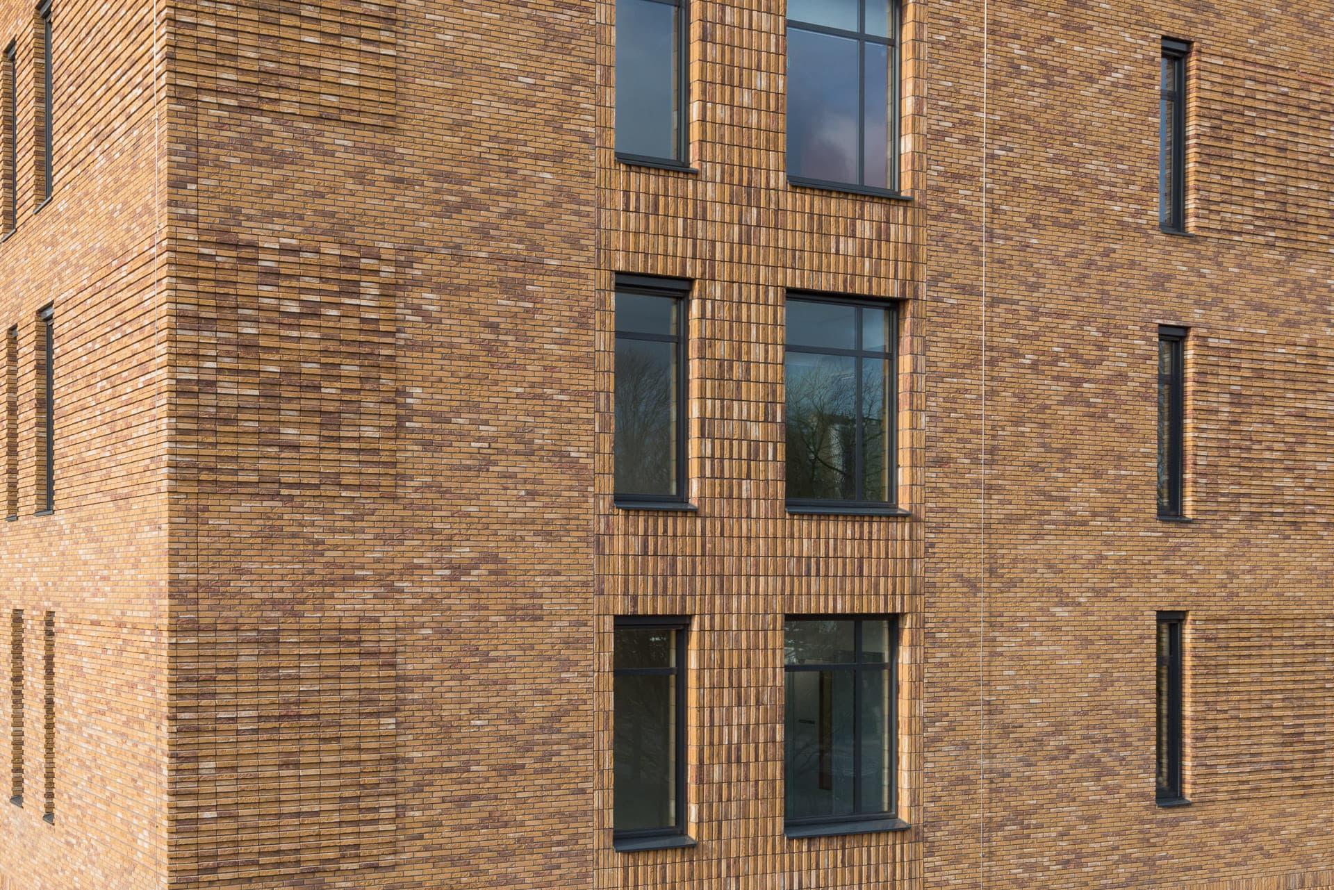 Verschillende type metselwerk op een gele gevel met zwarte ramen