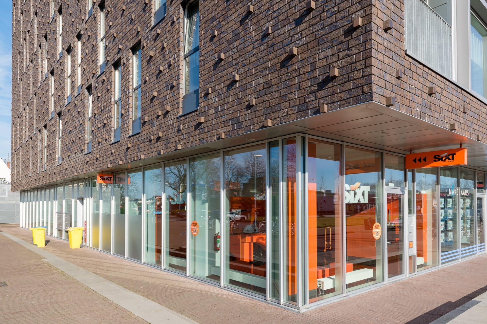 Gevel met uitstekende elementen bij Kop van Oost in Groningen met onderin een winkel