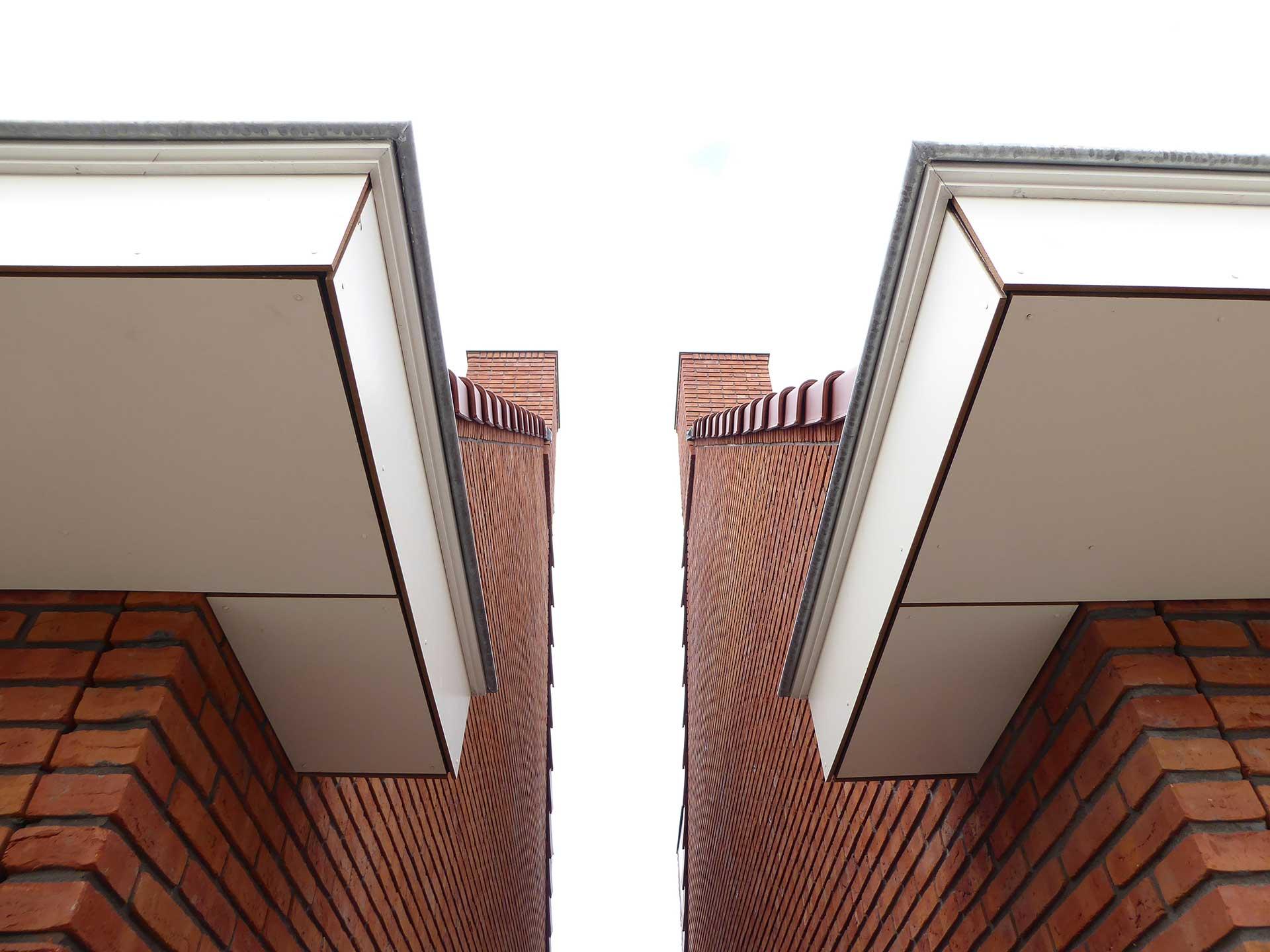 Havenbuurt Zaandam doorkijkje tussen twee huizen met dakgoten en rode baksteen