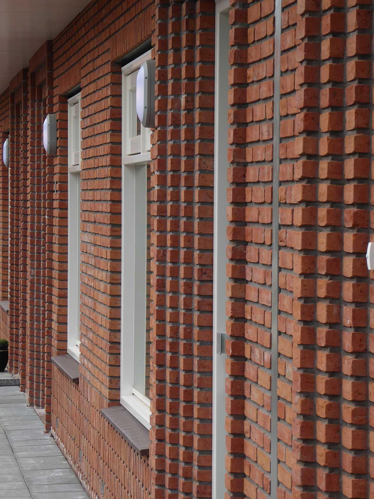 Havenbuurt Zaandam zicht op rij met voordeuren en ramen rond bijzonder metselwerk