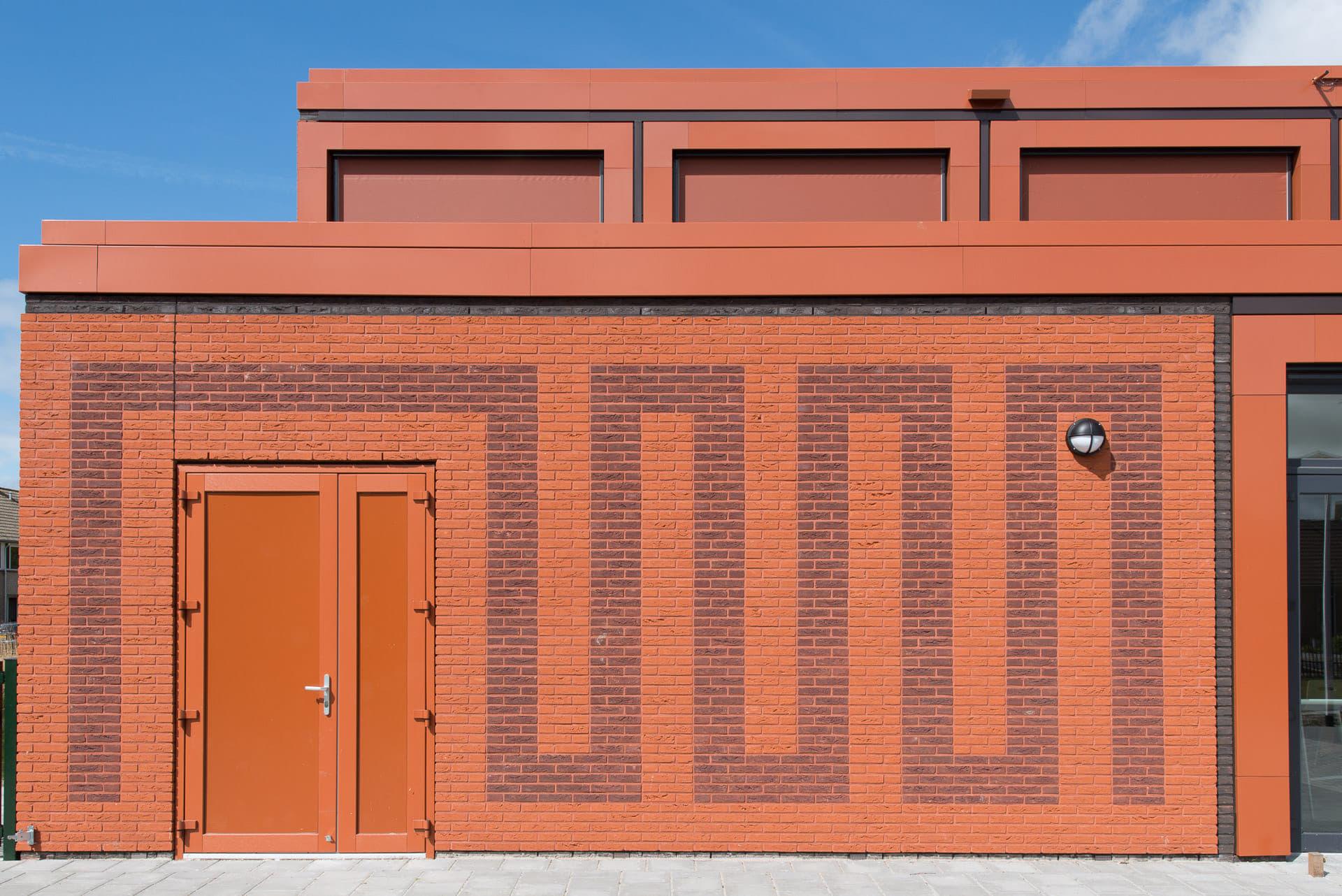Rode gevel met tekening in het metselwerk en een rode deur