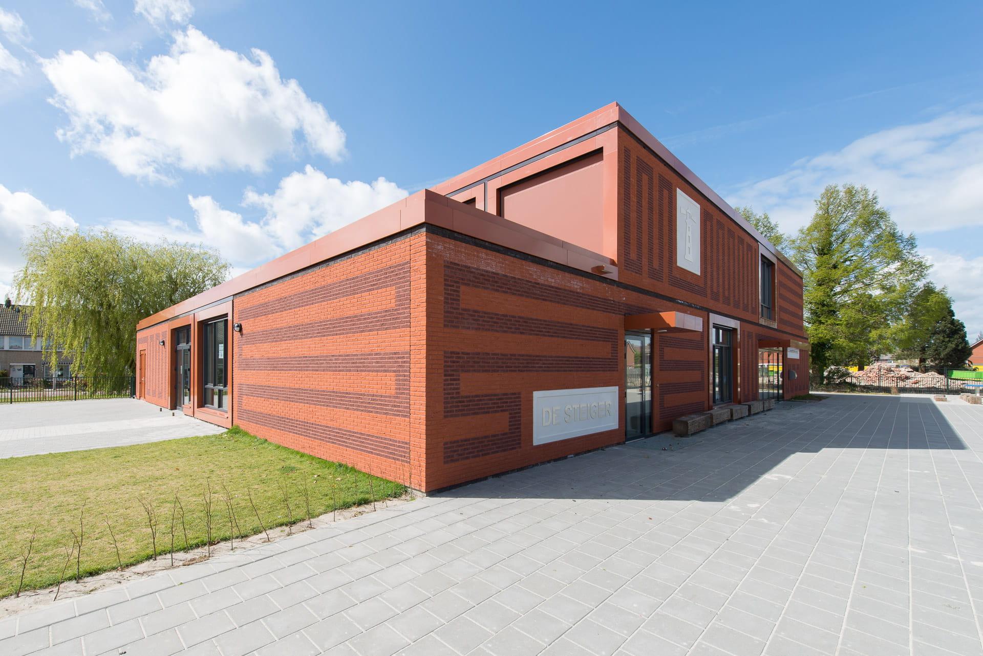 Hoek van MFA Lemstervaart, een rood gebouw met rode voeg en tekeningen in het metselwerk en op de voorgrond een plein
