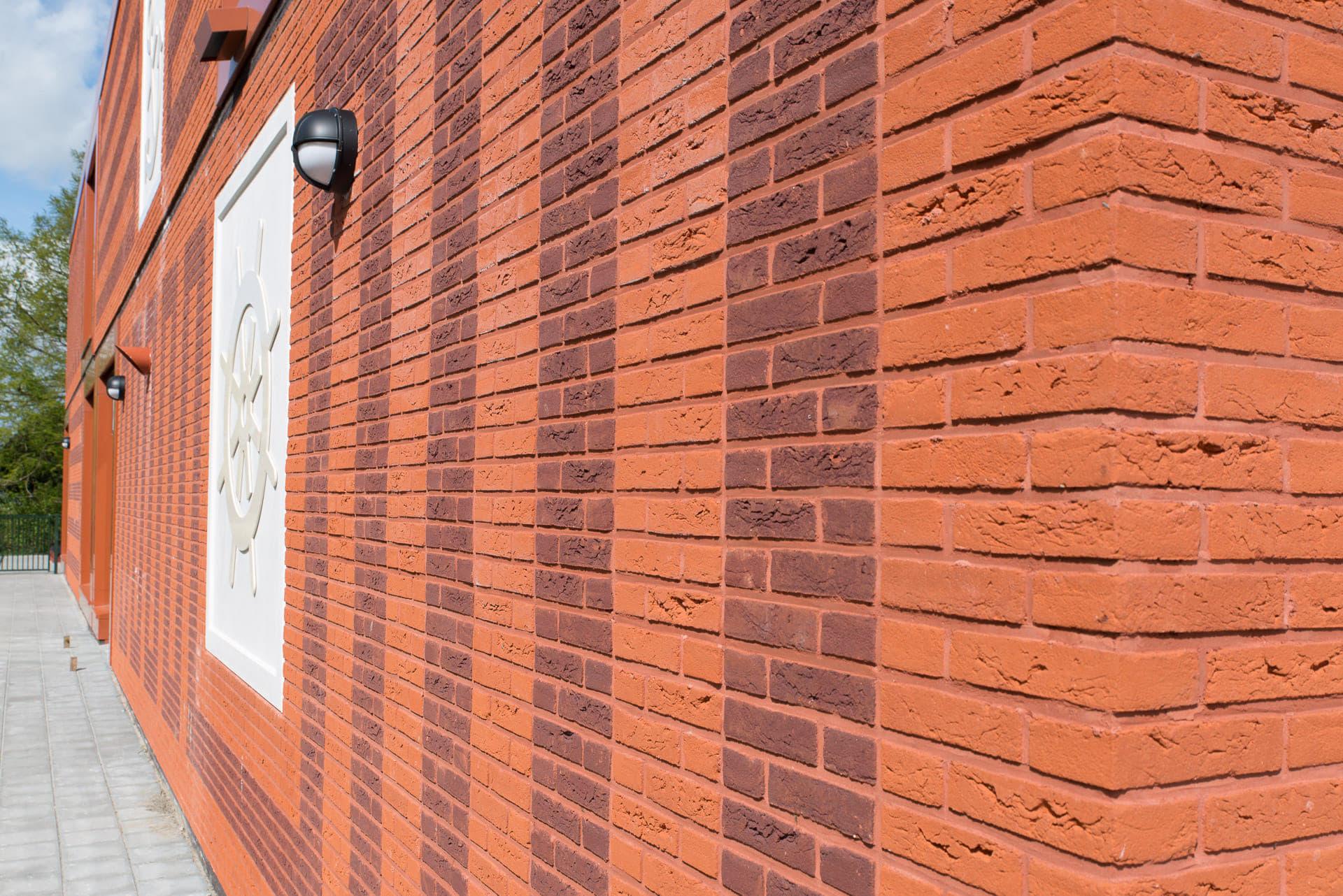 Hoek van muur met rode bakstenen en tekening van donkere stenen erin