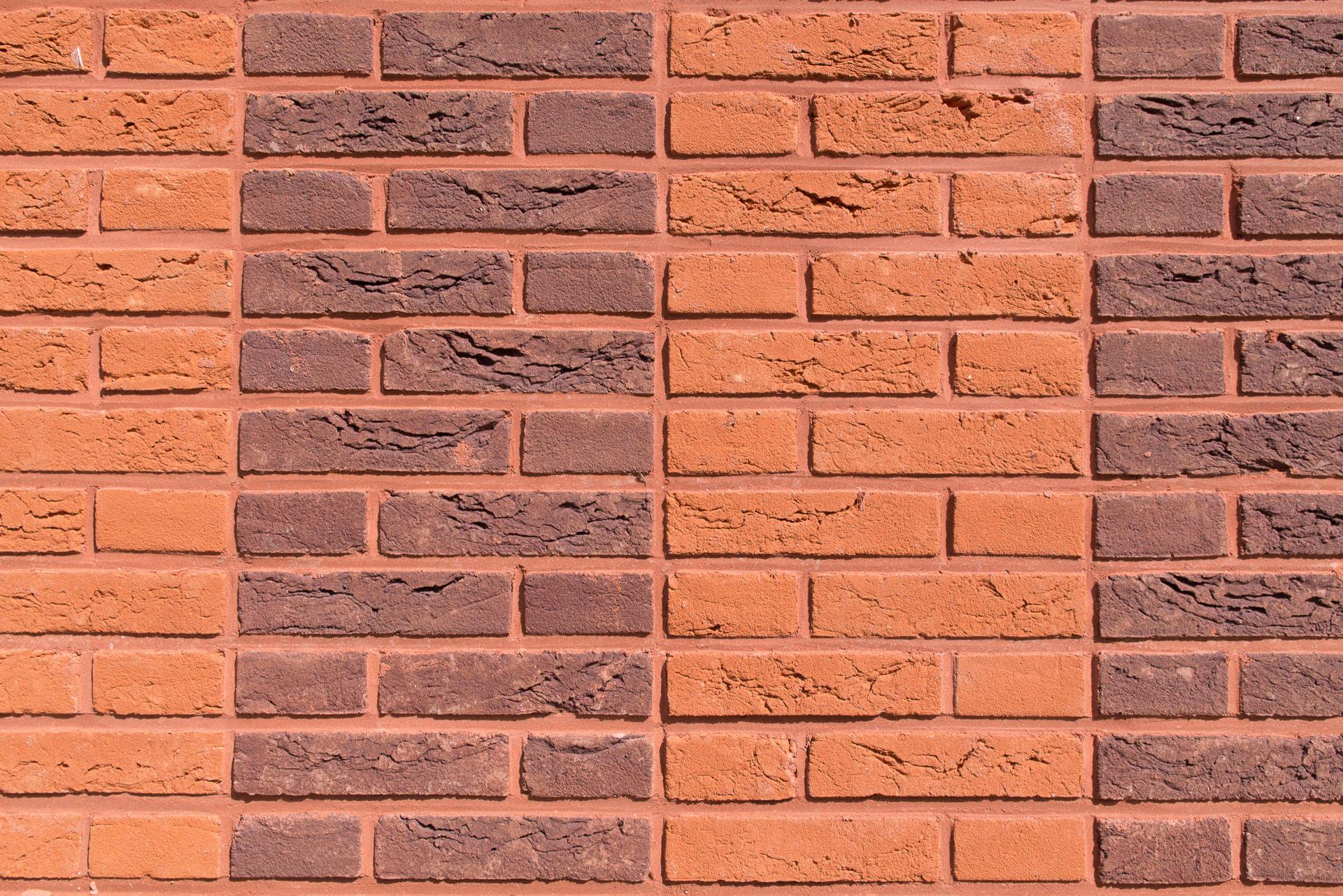 Detail van muur met verschillende kleuren baksteen in strakke rijen