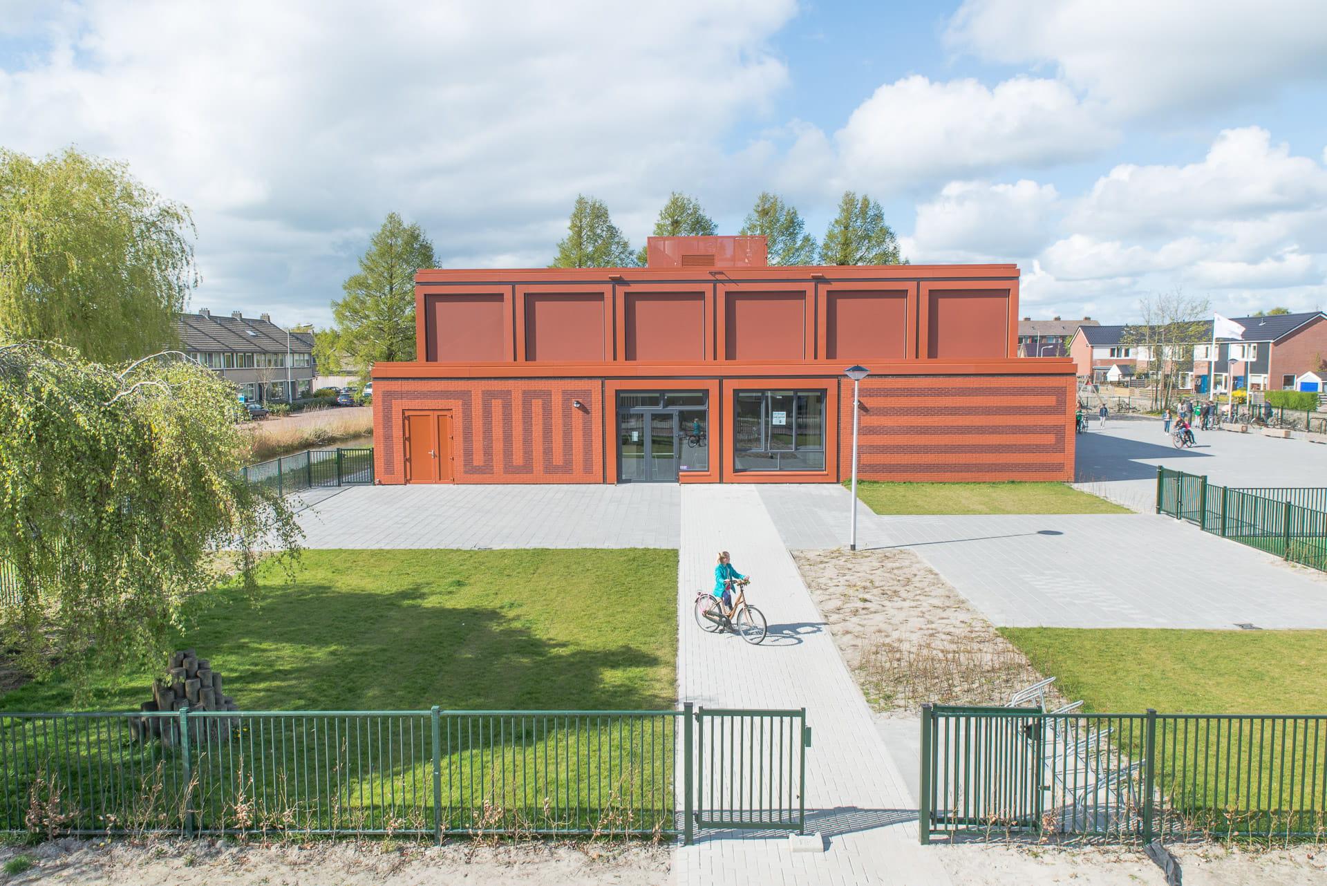 Vooraanzicht van rood gebouw met rode voeg en tekening in het metselwerk en plein op de voorgrond met fietser