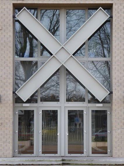 Stedelijk Gymnasium Breda met deuren en grote ramen met een groot kruis erdoorheen