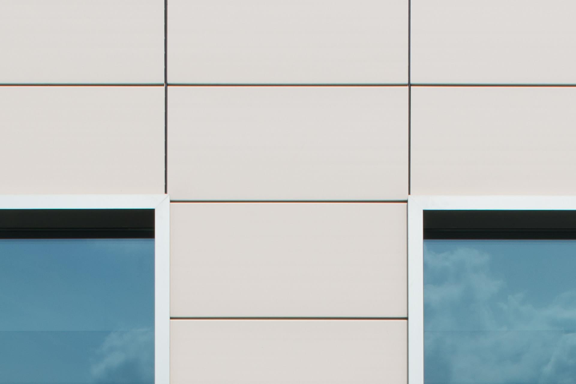Detail van lichte tegels aan de gevel tussen twee ramen