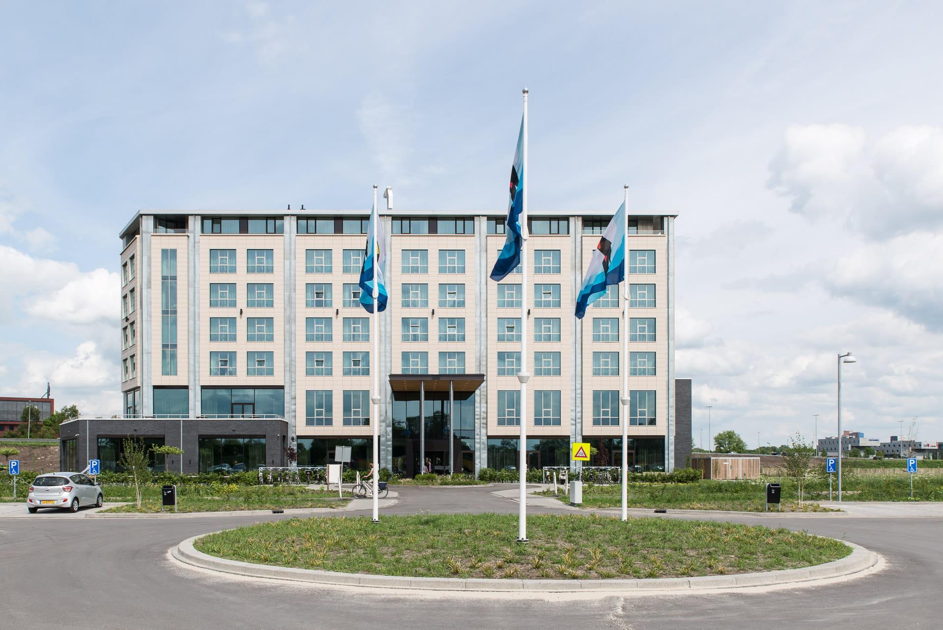 Witte gevel van het Van der Valk hotel met een rotonde op de voorgrond waarin 3 vlaggenmasten staan.