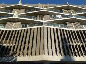 Zicht van onderen op een bruine gevel van een hoog gebouw met schuine lijnen en ramen