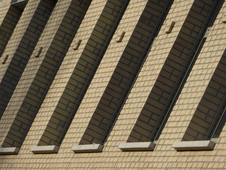Detail van smalle hoge ramen en licht metselwerk