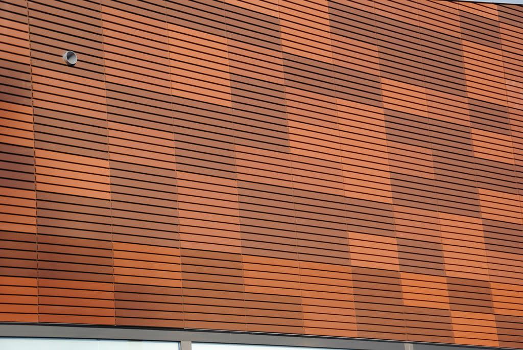 Detail van een muur met oranje en bruine argetontegels