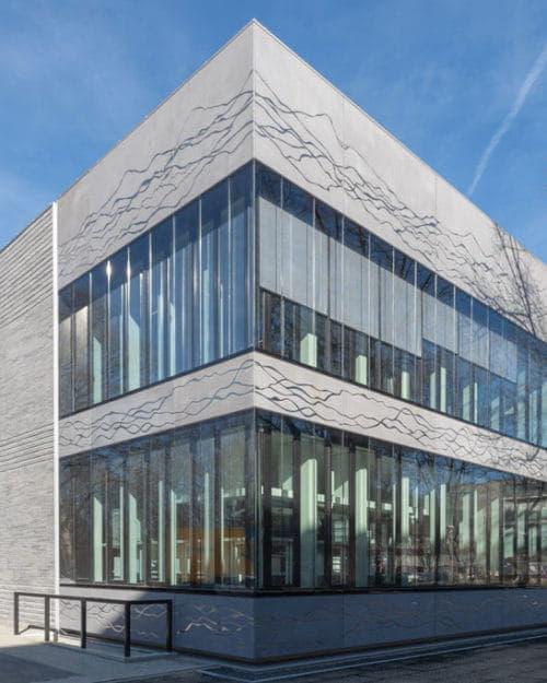 Zijaanzicht van een gebouw met lichtgrijze betonstrips en glas