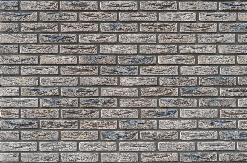 Detail van een muur met grijze stenen met gemeleerde kleuren