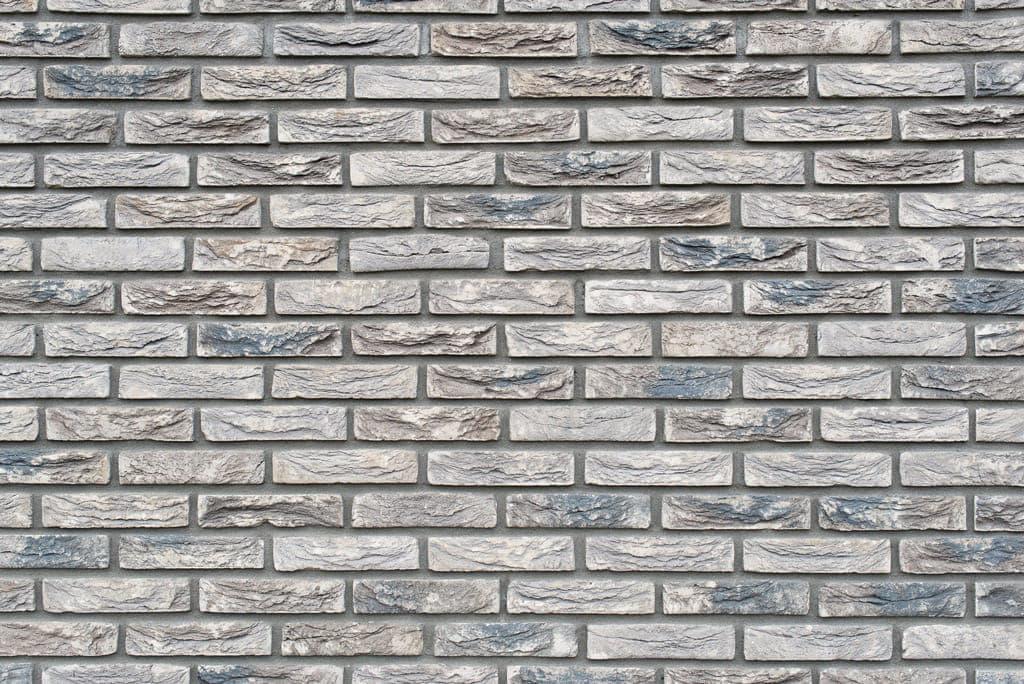 Detail van grijze stenen met grove structuur en kleuren
