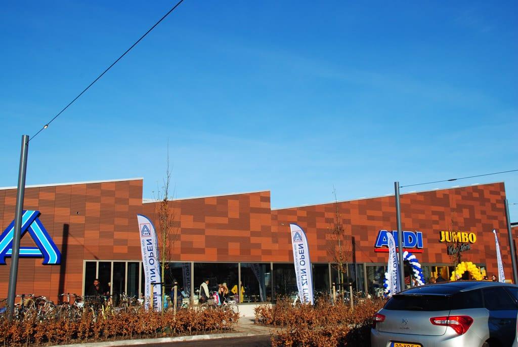 Gevel met lichtbruine Argeton aan het Molenplein Heerenveen met logo van winkels erop