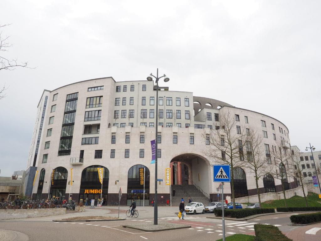Buitenkant van het Maankwartier in Heerlen, een rond gebouw met bogen en een wittige gevel