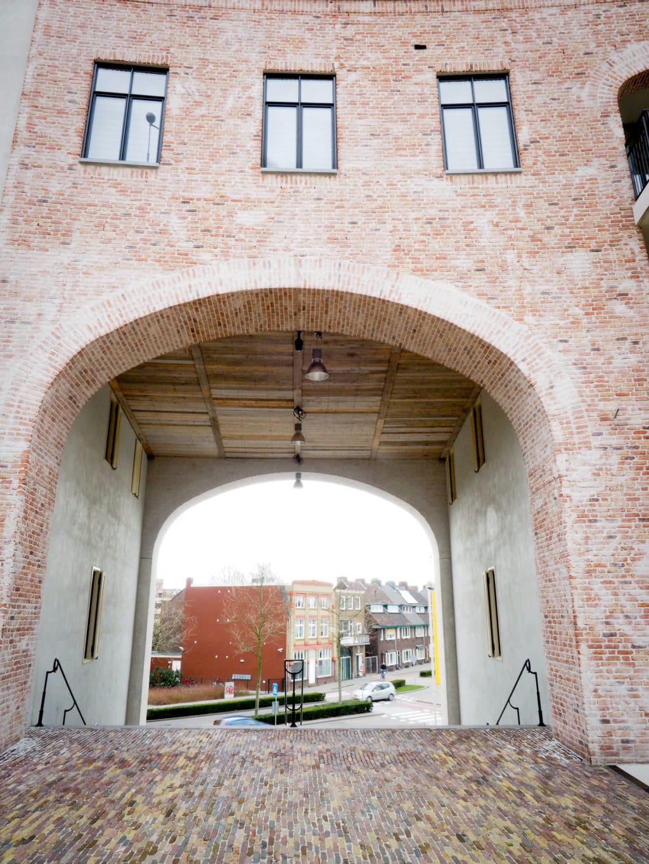 Boog of poort in een gevel met erboven ramen en een trap voor de gevel