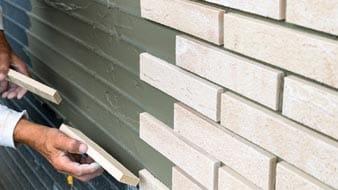 Witte steenstrips worden op een muur geplakt door een hand