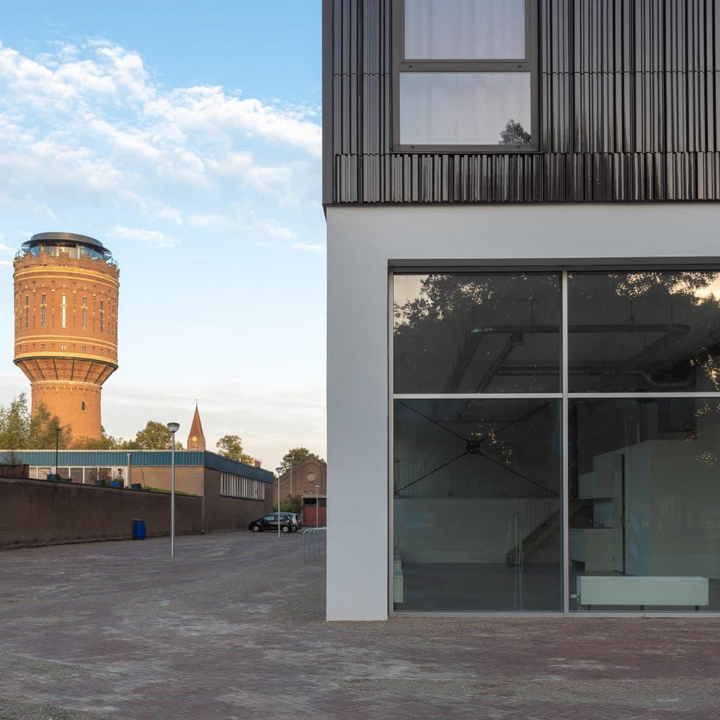 Closeup van gebouw met aan de bovenkant Argeton en eronder grote ramen. Ernaast een lichtrode watertoren in de verte