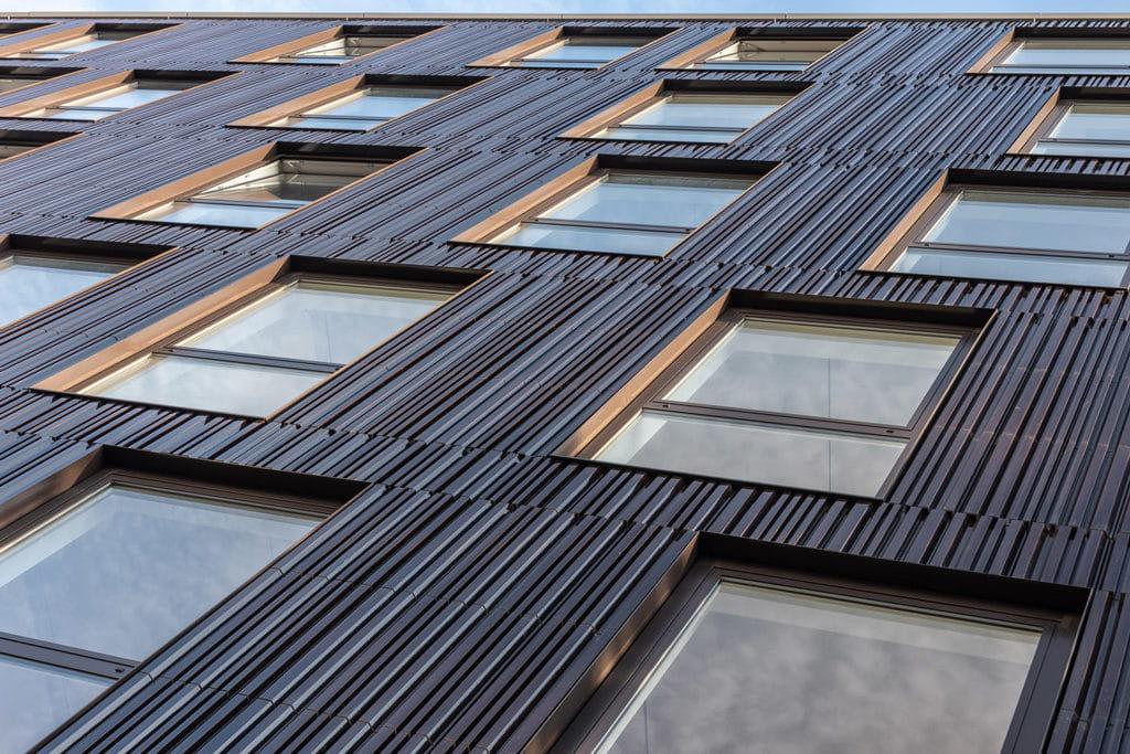 Detail van een gevel met ramen, van onderen genomen. De tegels zijn bruinig met een patroon