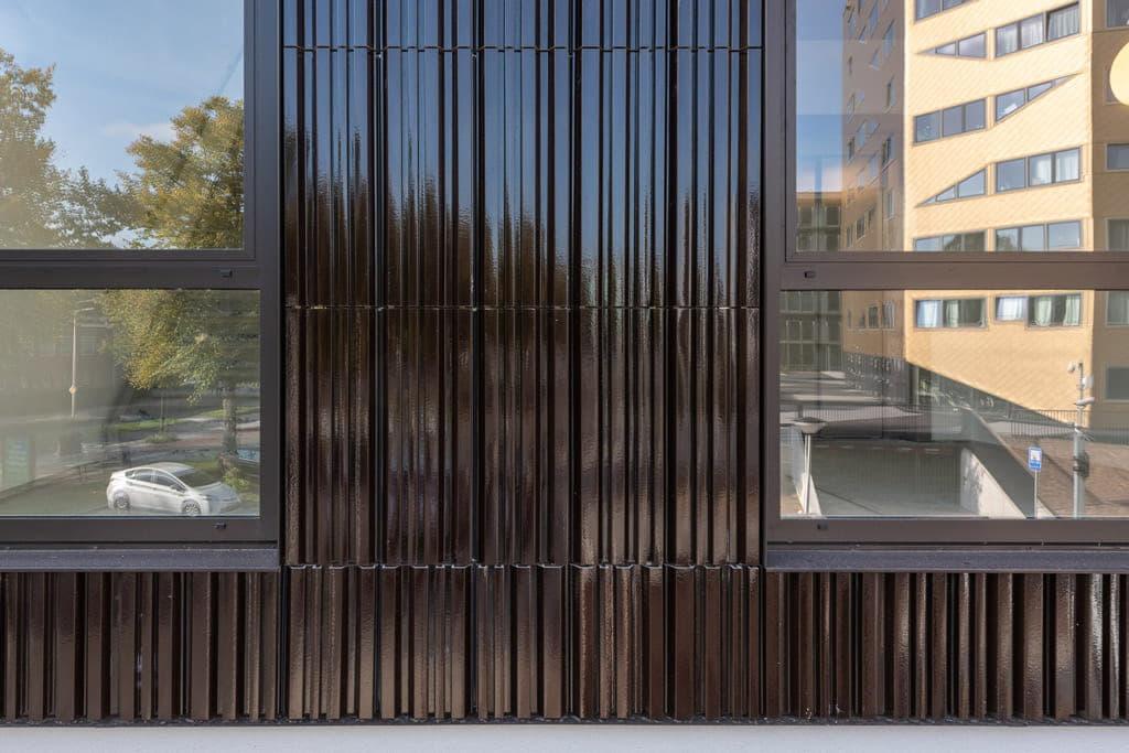 Detail van tegels van bruin argeton en ramen aan beide kanten
