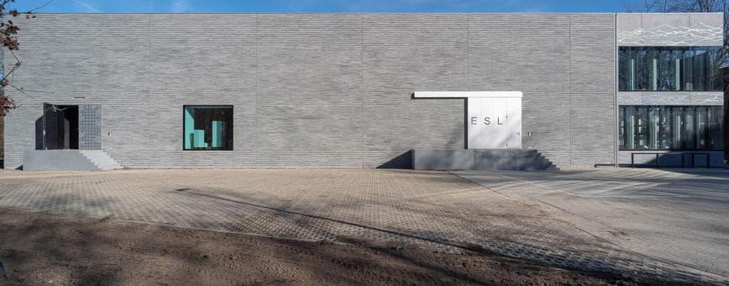 Overzichtsfoto van ESL Utrecht met grijze steenstrips en ramen, deuren en trappen ervoor