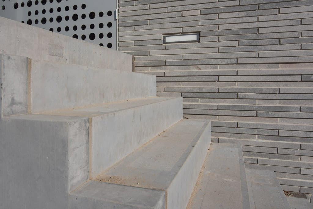 Trap naast een muur met betonnen steenstrips bij ESL Utrecht