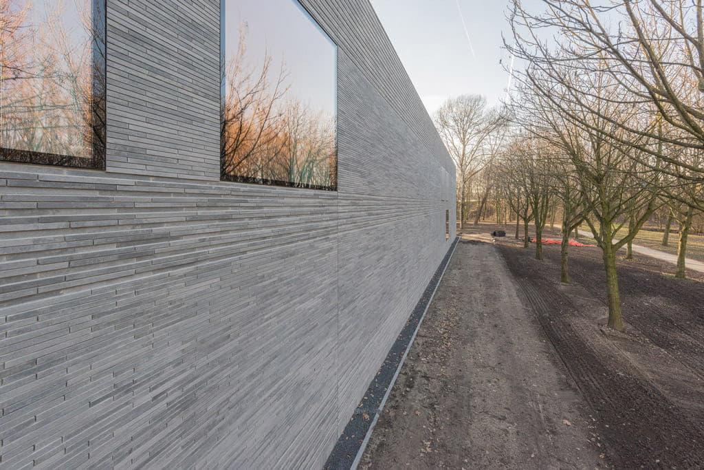 Muur van ESL in Utrecht met lange betonnen steenstrips, bomen en een pad ernaast