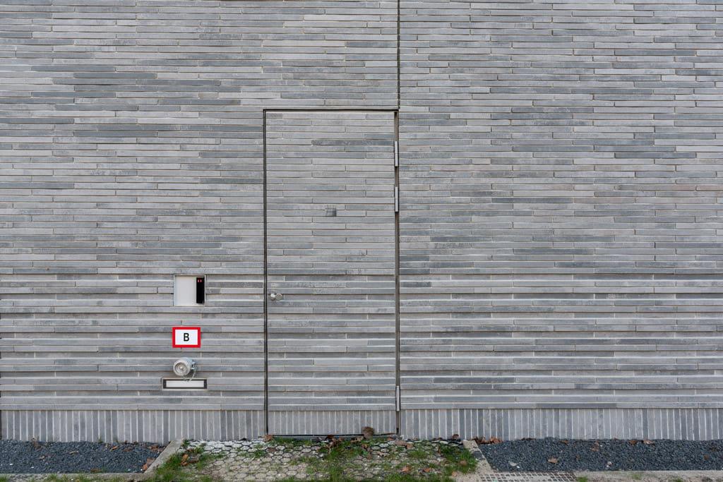 Detail van gevel met betonnen steenstrips langformaat, met een deur in de gevel