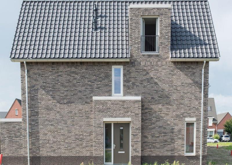 zijaanzicht van een grijsbruin huis met dakpannen