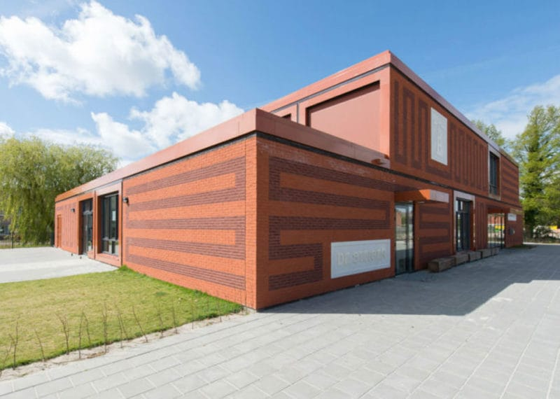 Rood gebouw met tekening in de gevel bij Lemstervaart