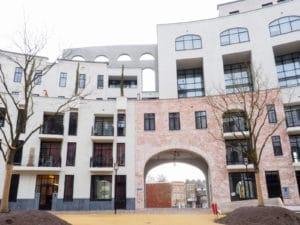 Zicht op een gebouw in wit en rood, met een boog van prefab in het midden