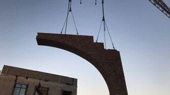 Prefab element hangt aan een hijskraan voor een gebouw