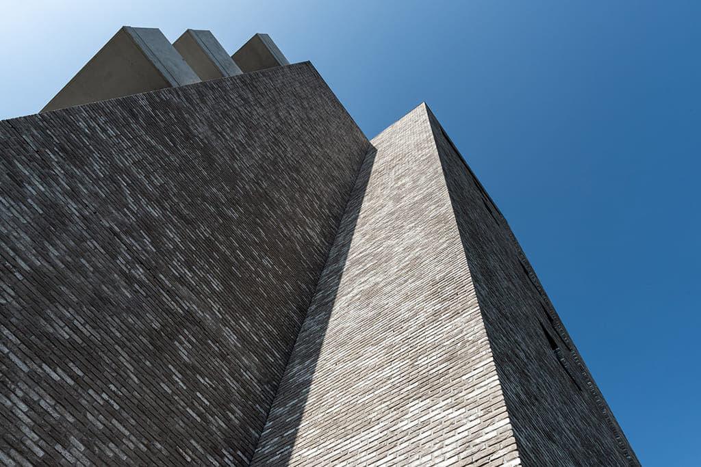 Appartementgebouw van onderen bekeken met een blauwe lucht