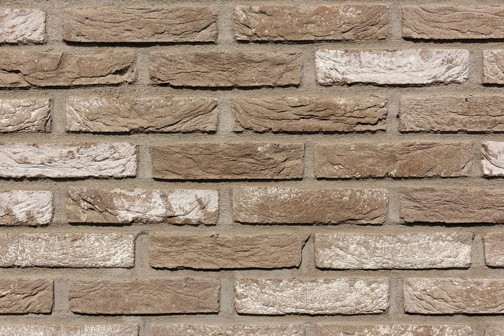 Detail van een muur met lichtbruine stenen en wittige stenen