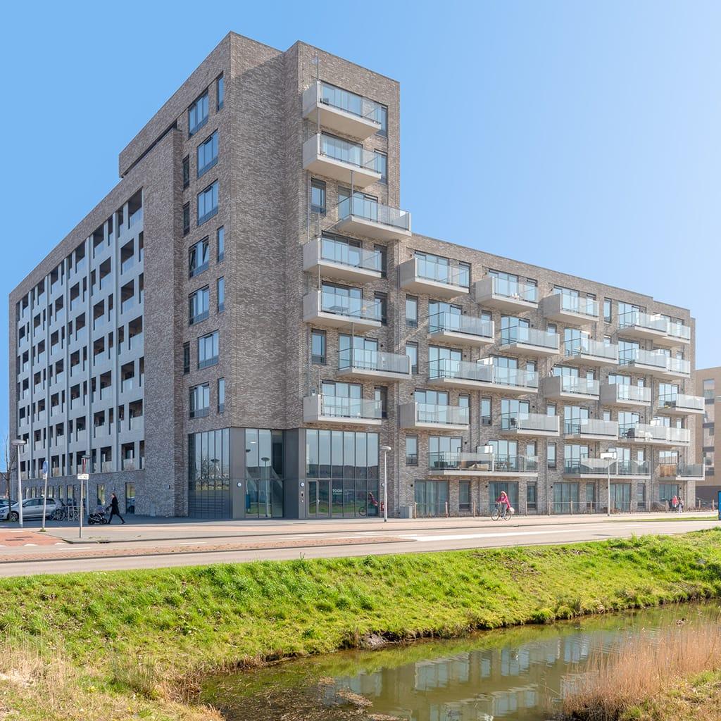 Hoek van een appartementencomplex met veel ramen en glazen balkons