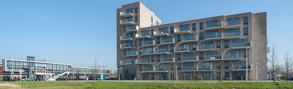 Overizchtsfoto met links een station in utrecht en rechts ene appartementgebouw met lichte baksteen