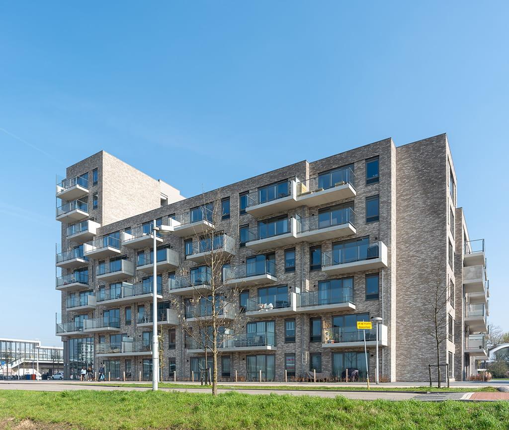 Overzicht van een appartementencomplex Toon in Utrecht met een lichte steen aan het station