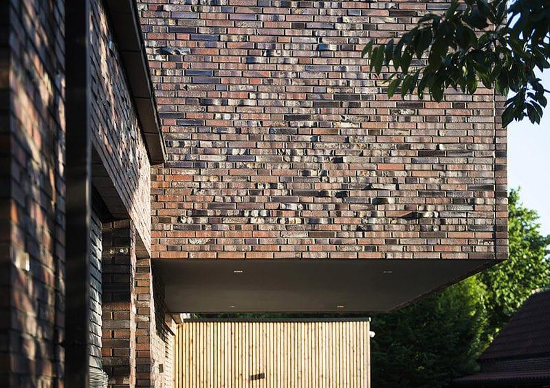 Muur met rough brick op een muur en een houten deur eronder