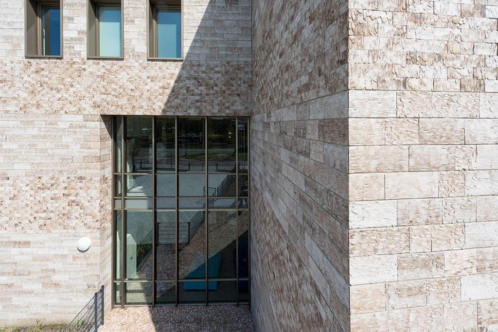 Hoek van het gebouw met ramen en schaduw op een lichte steen