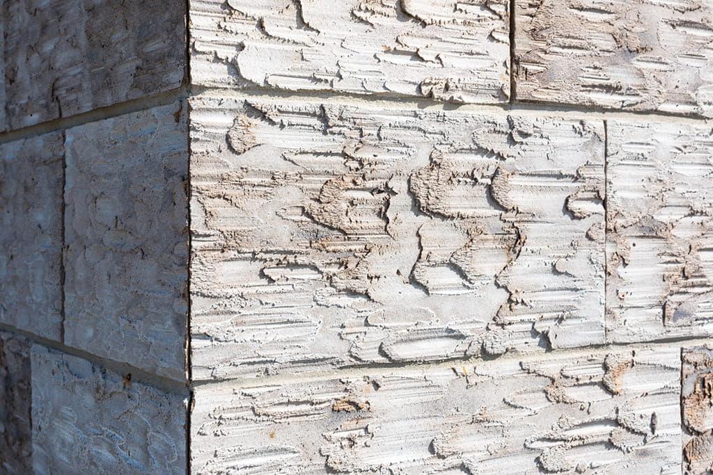Detail van een hoek van een gele robuuste gevelsteen de clickbrick