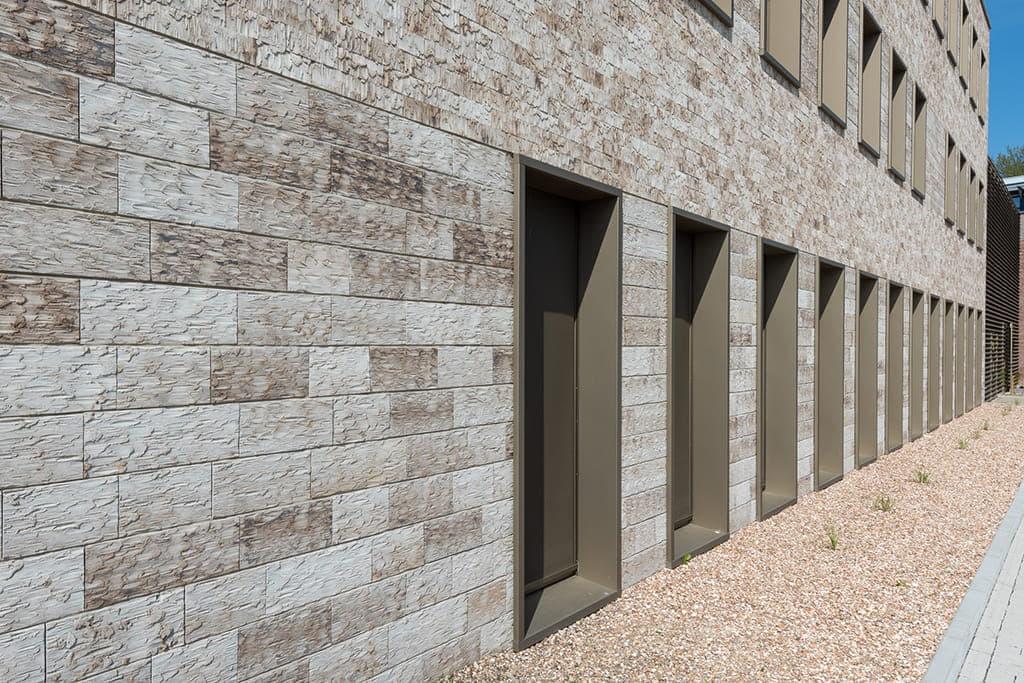 Lange rij met ramen tot op de grond in een gebouw met lichte steen