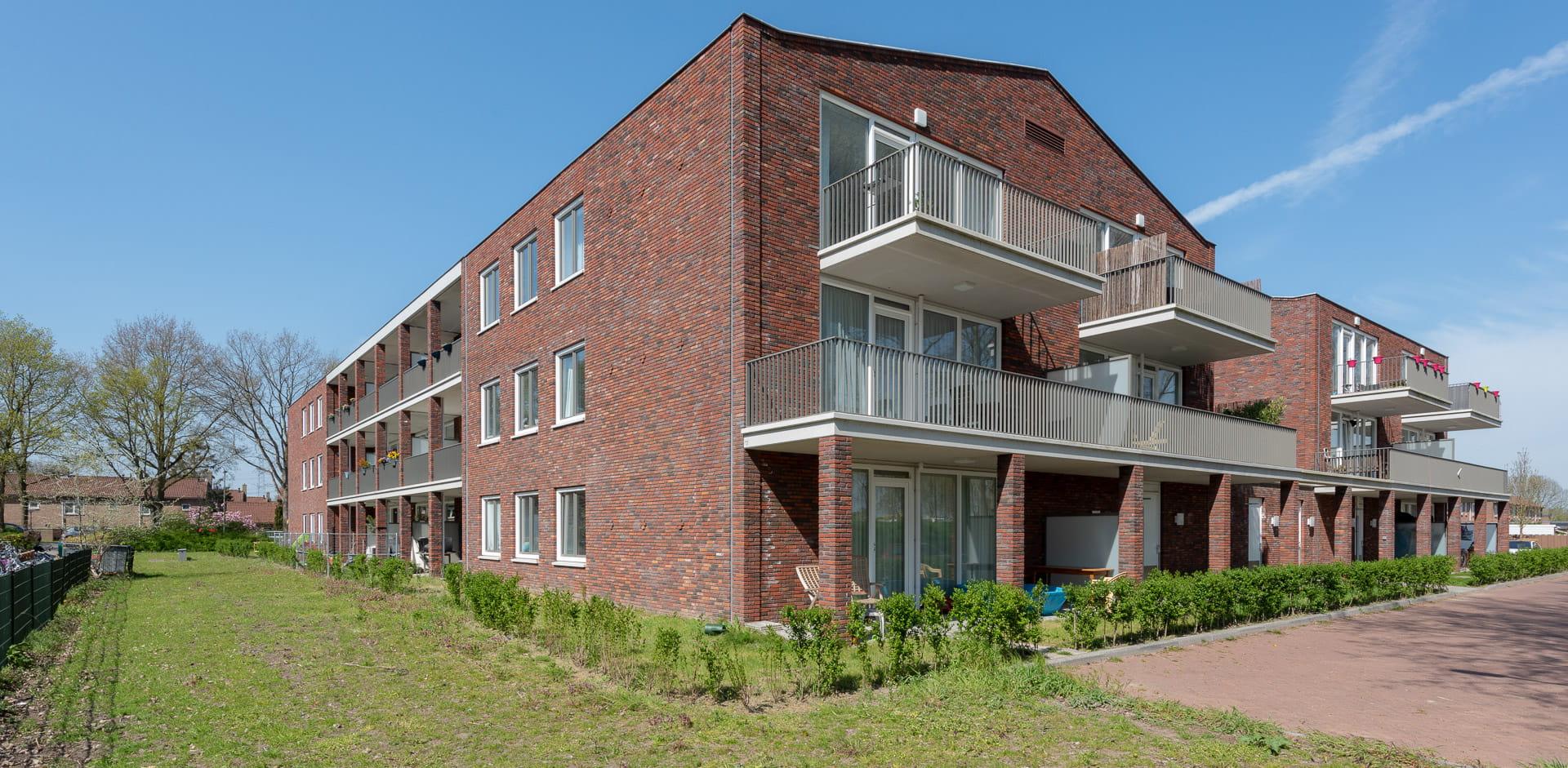 Roodbruikn gebouw met balkons schuin bekeken tegen een blauwe lucht