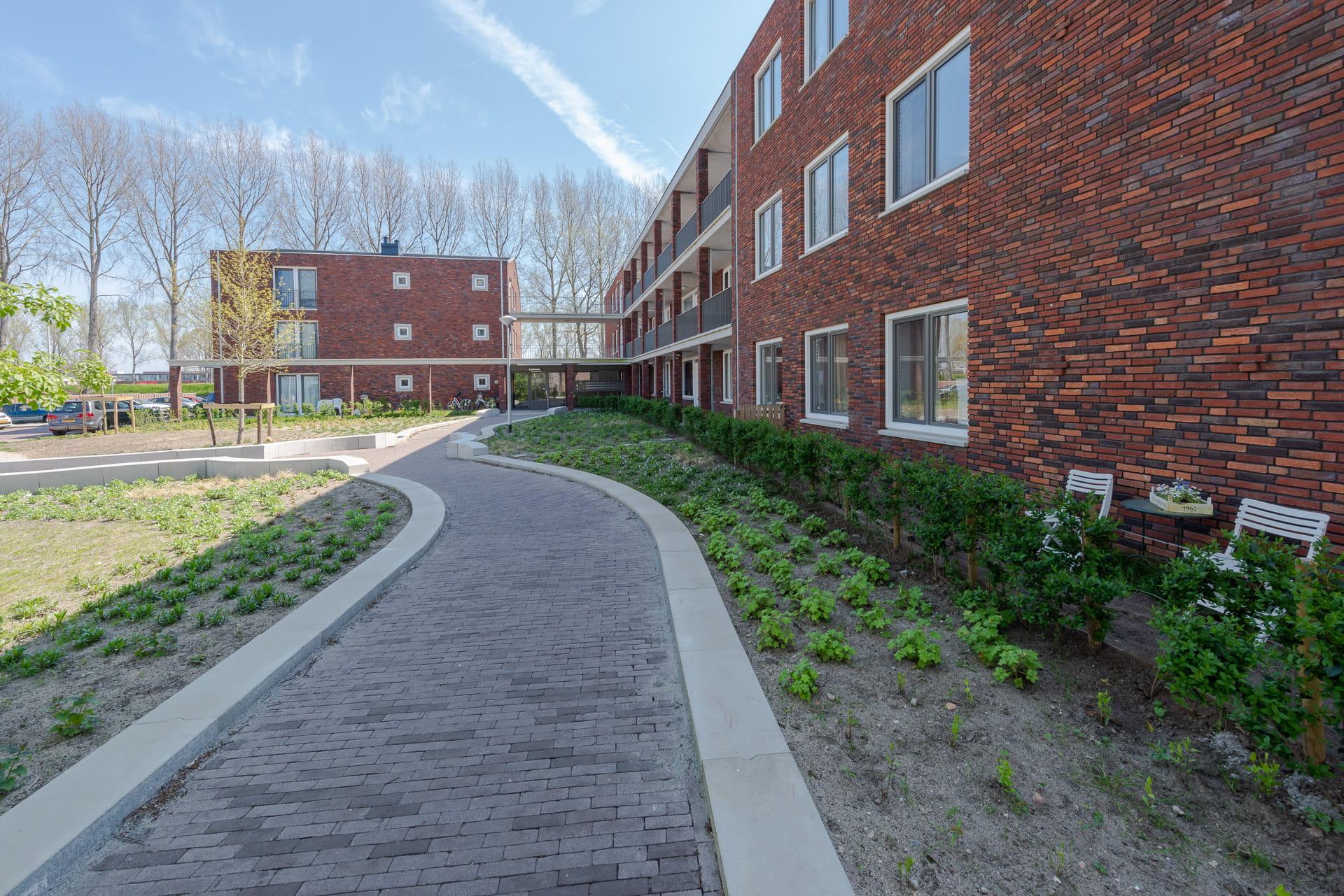 Roodbruin gebouw naast een slingerend pad met op de achtergrond nog een gebouw en bomen