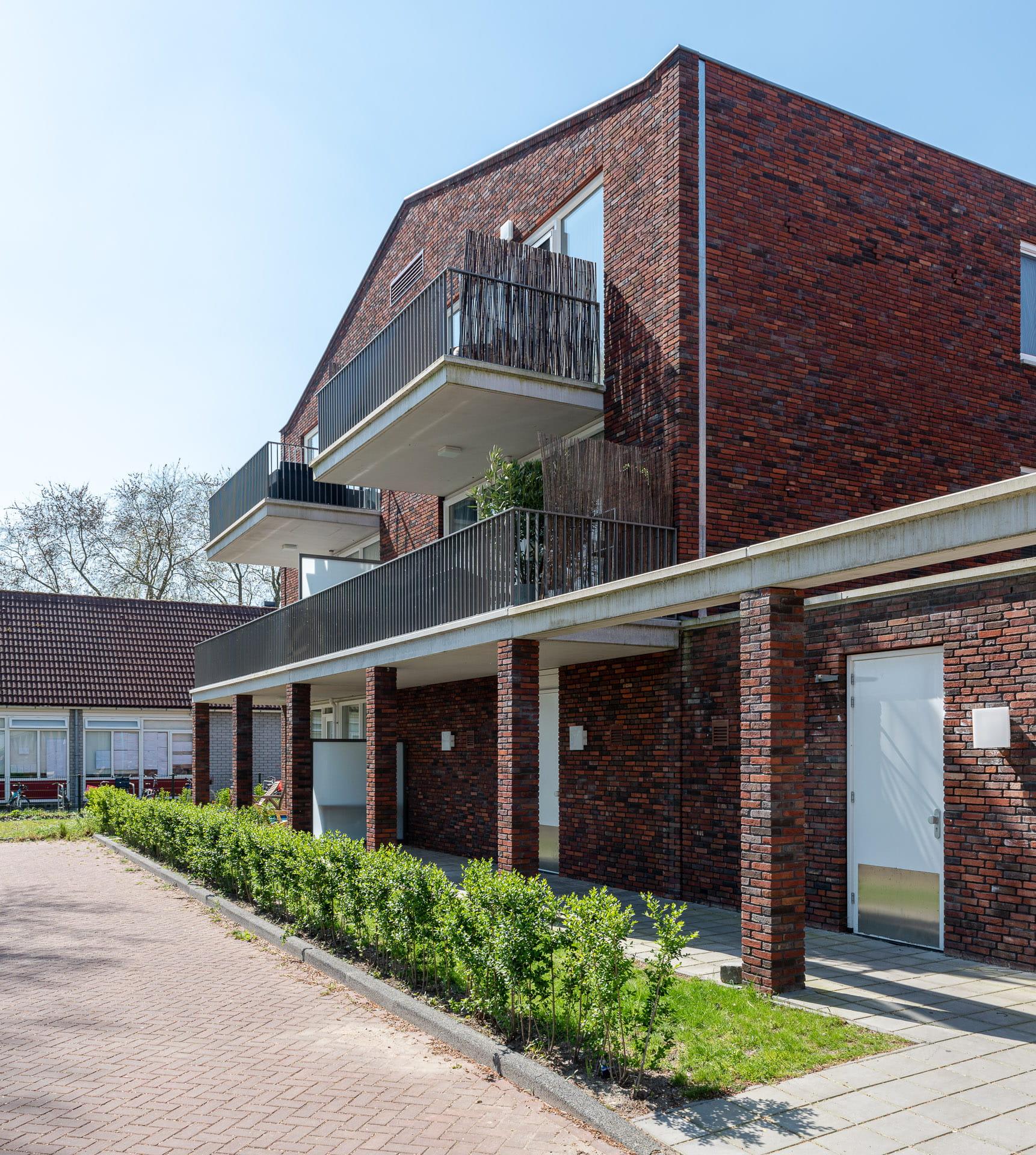 roodbruin gebouw met een balkonrij en groenstrook ervoor