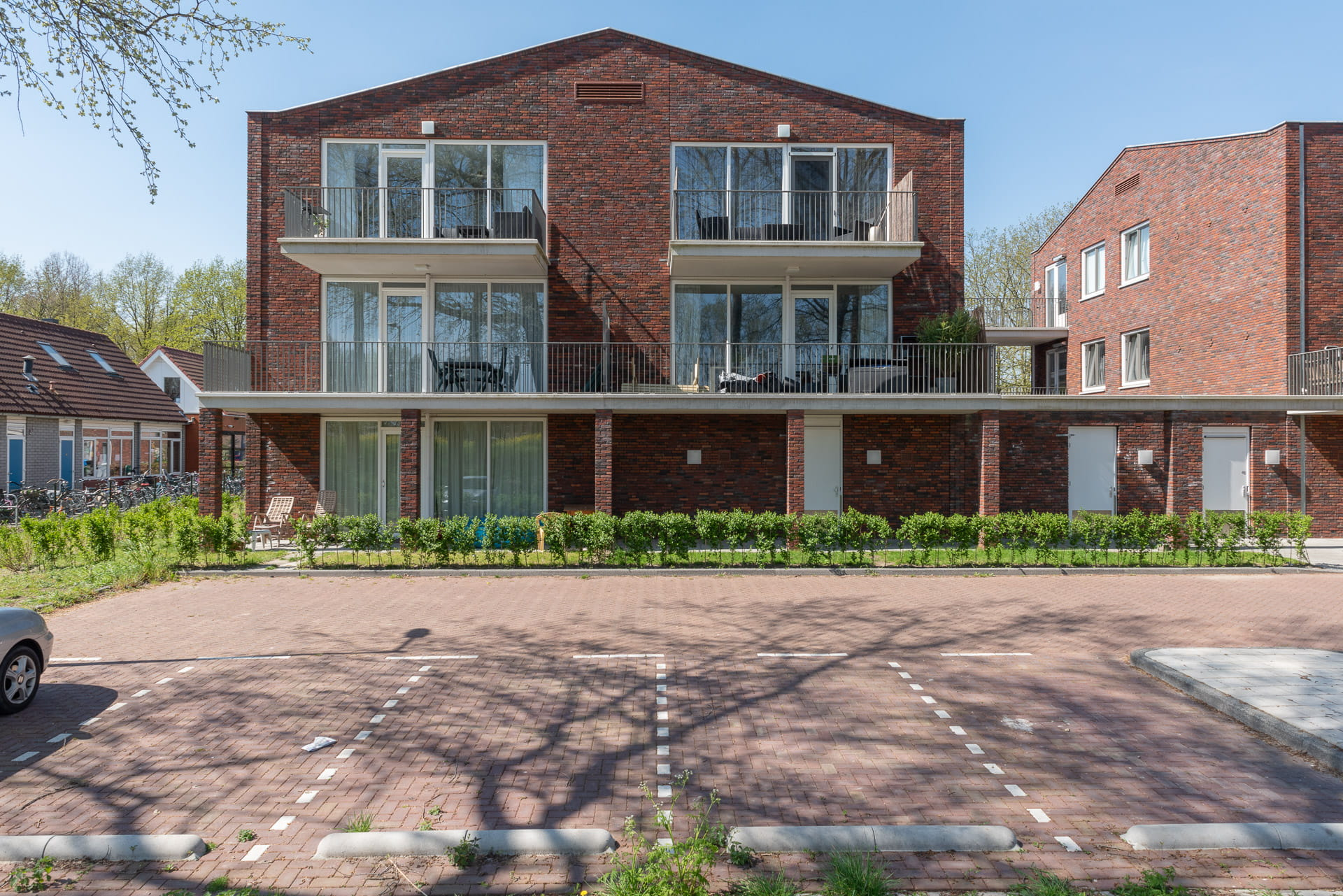Rechte aanblik van een roodbruin gebouw met een puntdak, ramen en balkons. Op de voorgrond parkeerplaatsen.